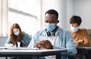 Student wearing mask looking at phone with personalized digital recruitment message