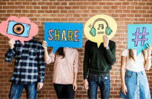 Four adults of various ages stand in front of a brick wall holding cardboard signs in front of their faces that depict social media activities.